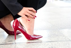 Woman sitting  catch her ankle foot and she has foot pain. Caused by wearing high heels red.Health and beauty concepts