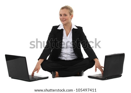 Woman sitting cross-legged in front of two computers - stock photo