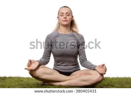 woman sitting cross legged on grass relaxing and doing yoga shot in the studio
