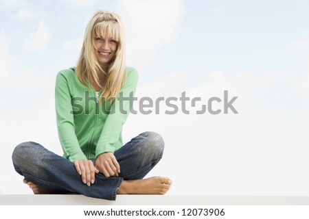 Woman sitting cross legged outside against blue sky