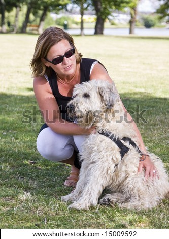 Woman sitting down, correcting a dog, outdoors in a park. - stock photo