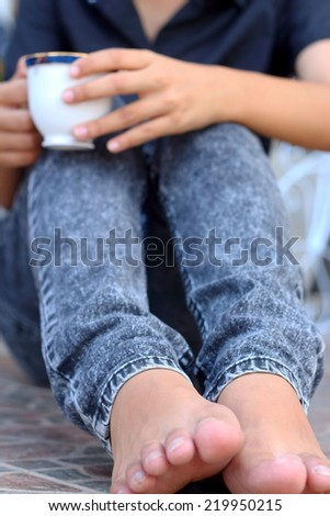 Woman sitting holding a coffee cup