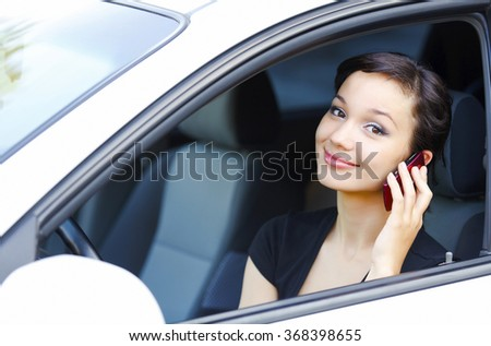 Woman sitting in a car and talking by mobile telephone  - stock photo