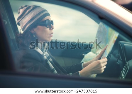 Woman sitting in a car looking at the map - stock photo