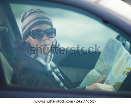 Woman sitting in a car with a map - stock photo