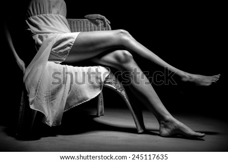 Woman sitting in a chair showing her legs - stock photo