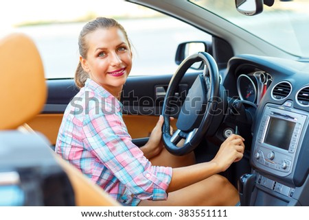 Woman sitting in a convertible and is going to start the engine - the concept of buying a used car or a rental car