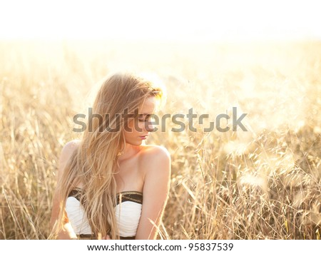 Woman sitting in a field with copy space provided - stock photo