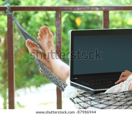 Woman sitting in a hammock in a garden with laptop - stock photo
