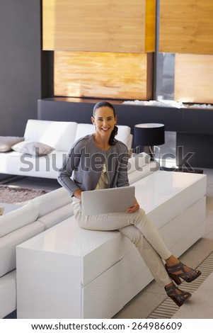 Woman sitting in a living room with laptop on her knees. - stock photo