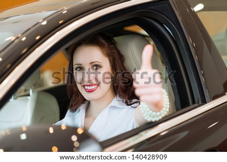 woman sitting in a new car, showing thumb up, focus on the face - stock photo
