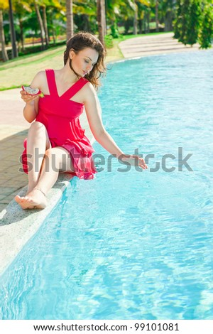 Woman sitting in a swimming pool and eating dragon fruit