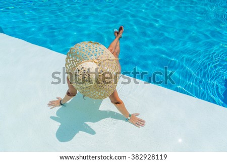Woman sitting in a swimming pool in a large straw sunhat