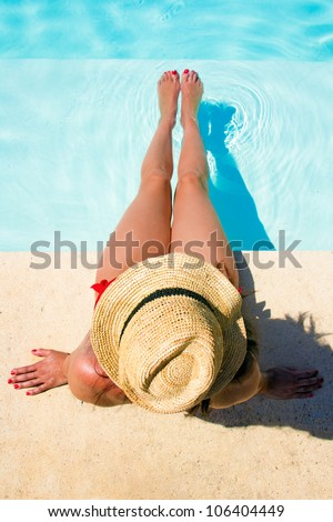 Woman sitting in a swimming pool with a sunhat - stock photo