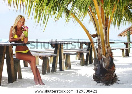 woman sitting in a tropical cafe on the background of a  palm trees and sky and sea - stock photo