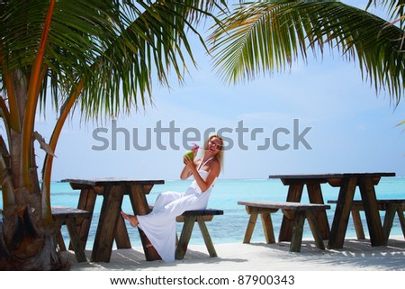 woman sitting in a tropical cafe on the background of a  palm trees and sky and sea