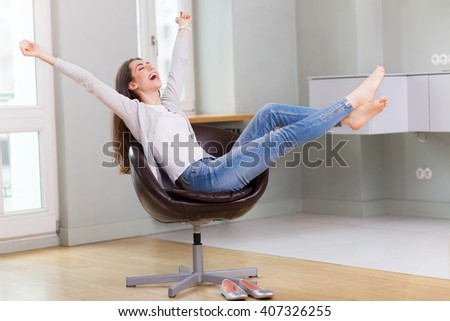 Woman sitting in armchair, arms outstretched  - stock photo