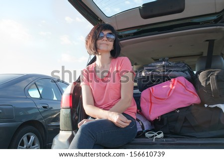 Woman sitting in back of car smiling. Getting ready to go