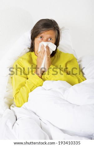woman sitting in bed blowing her nose - stock photo