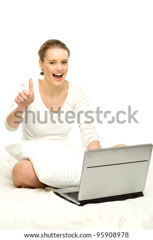 Woman sitting in bed with laptop - stock photo
