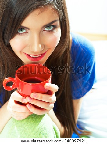 Woman sitting in bed with red coffee cup. Smiling young model portrait.