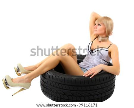 Woman sitting in car wheel - stock photo