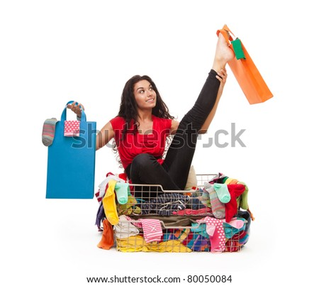 Woman sitting in clothes basket in flexible pose with shopping bags