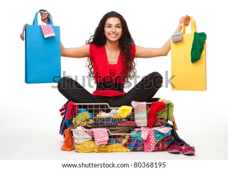 Woman sitting in clothes with shopping bags in her hands and big smile