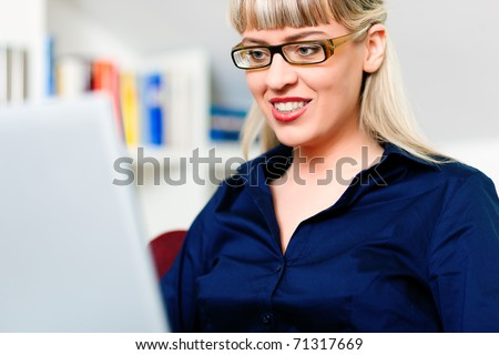 Woman sitting in front of a bookshelf using her telephone, working with a laptop in the internet from home, she is a telecommuter - stock photo