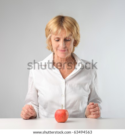 Woman sitting in front of an apple - stock photo
