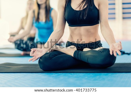 Woman sitting in full lotus position on Yoga class - stock photo