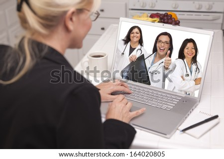 Woman Sitting In Kitchen Using Laptop Viewing Team of Hispanic Female Doctors or Nurses with Thumbs Up Holding X-ray. - stock photo