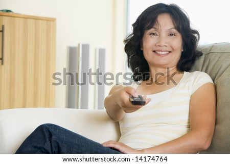Woman sitting in living room holding remote control smiling - stock photo