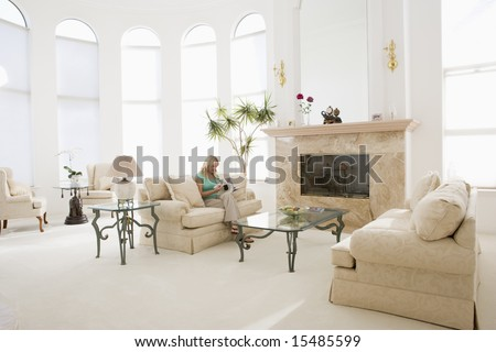 Woman sitting in living room in luxurious home - stock photo