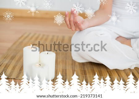 Woman sitting in lotus pose beside white candles against fir tree forest and snowflakes - stock photo