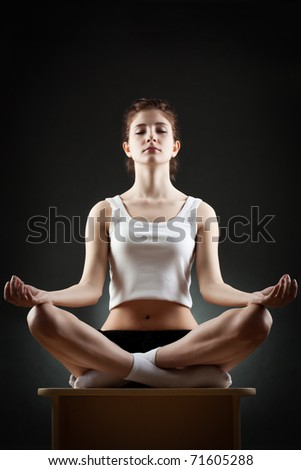 woman sitting in lotus pose over dark background