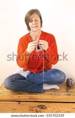woman sitting in lotus position and knitting