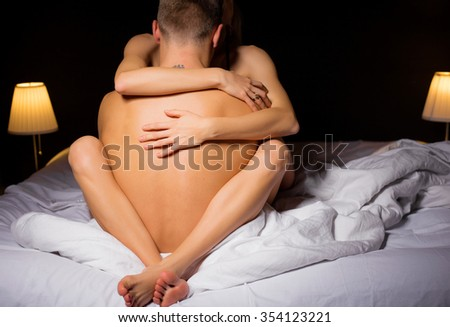 Woman sitting in mans lap and hugging him  - stock photo