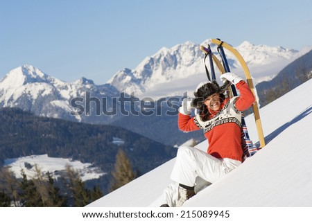 Woman sitting in snow, leaning on sledge - stock photo