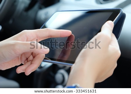Woman Sitting in the Car and Using digital tablet.Business technology concept.  - stock photo