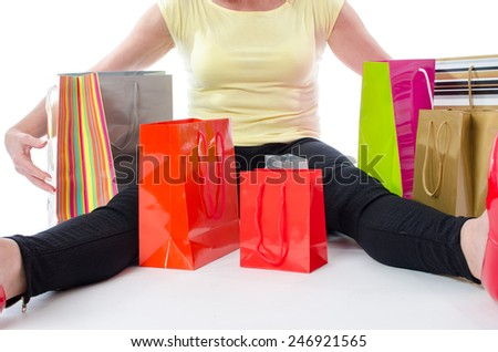 Woman sitting in the middle of shopping bags, isolated on white