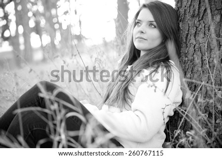 Woman Sitting In The Park - This is a black and white shot of a beautiful young woman sitting in some tall grass next to a tree enjoying the nice weather. Shot with a shallow depth of field. - stock photo