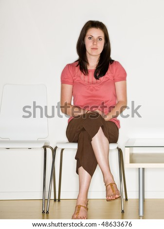 Woman sitting in waiting room - stock photo