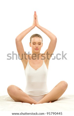 Woman sitting in yoga position in bed - stock photo