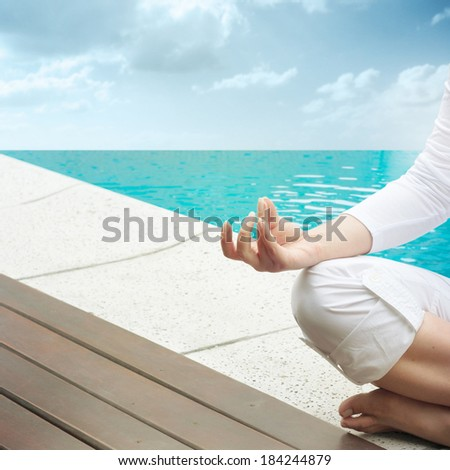 Woman sitting in yoga position on terrace by infinity pool