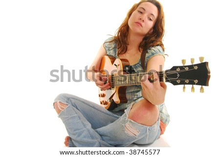 Woman sitting Indian style playing a guitar, isolated on white.