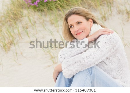 Woman sitting near the sandy hill at the beach - stock photo