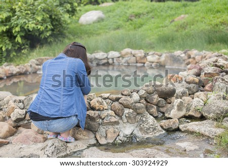 Woman sitting nearby while moke rising from hot springs in Lampnag, Northern of Thailand