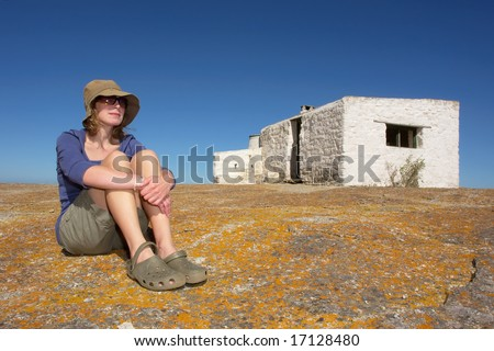 Woman sitting next to abandoned house next to sea. Shot in West Coast Nature Reserve, near Langebaan, Western Cape, South Africa. - stock photo