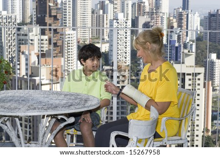 Woman sitting next to boy on balcony overlooking city. Woman and boy talking. Horizontally framed photo. - stock photo